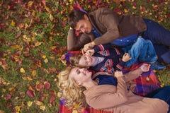 HOOGSTE MENING: Portret van gelukkige jonge ouders met zoon op een plaid in park Royalty-vrije Stock Foto