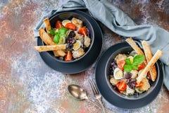 Hoogste mening twee porties van Caesar-salade met kip, kwartelsei, kersentomaten, croutons en basilicum in donkerblauwe kommen op stock afbeeldingen