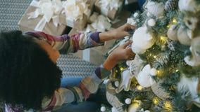 Hoogste mening van Aantrekkelijke jonge Afrikaanse vrouw die Kerstboom verfraaien die thuis voor Kerstmisviering voorbereidingen  royalty-vrije stock fotografie
