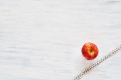 Hoogste mening van appel en maatregelenband op witte houten achtergrond Stock Afbeeldingen