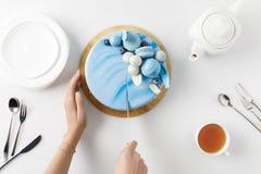 hoogste mening van bebouwde handen die cake op hakbord snijden stock afbeeldingen
