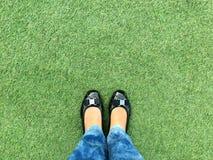Hoogste mening van been die van vrouw zwarte toevallige schoenen dragen die zich op het groene gras bevinden Royalty-vrije Stock Afbeeldingen