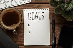 Hoogste mening van blocnote met Doelstellingen Lijst, kop van koffie op houten lijst, doelstellingen concept Stock Fotografie