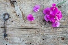 Hoogste mening van bloemen en oude sleutel op houten vloer stock afbeeldingen