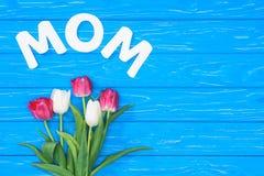 hoogste mening van boeket van roze en wit tulpen en woordmamma op blauwe lijst, het concept van de moedersdag stock afbeeldingen