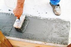 Hoogste mening van bouwvakker die verfborstel voor het toepassen van waterdicht dichtingsproduct gebruiken stock fotografie
