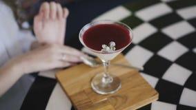 Hoogste mening van cocktailgelei het spinnen in vrouwelijke handen 4K stock video