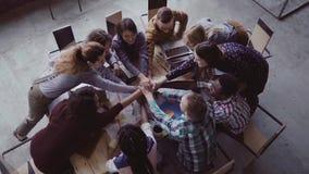 Hoogste mening van commercieel team die op kantoor werken De jonge gemengde rasgroep mensen brengt palm op centrum samen Langzame stock footage