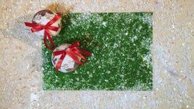 Hoogste mening van dalende sneeuw op de groene achtergrond whith Kerstmisballen stock videobeelden