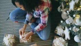 Hoogste mening van de Aantrekkelijke gemengde doos van de de verpakkingsgift van het rasmeisje dichtbij Kerstboom thuis stock foto's