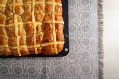 Hoogste mening van de eigengemaakte hete dwarsbroodjes van Pasen op bakselpan tegen kleurrijk tafelkleed Royalty-vrije Stock Foto