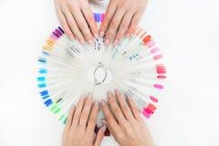 Hoogste mening van de handen van de mooie vrouw met inzameling van de steekproeven van het kleurennagellak op witte achtergrond royalty-vrije stock afbeelding