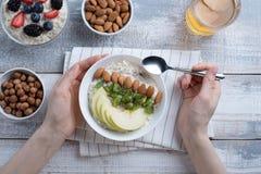 Hoogste mening van de handen van vrouwen in Ontbijt, havermeel met amandelen en Apple, noten, bessen, compote royalty-vrije stock afbeeldingen