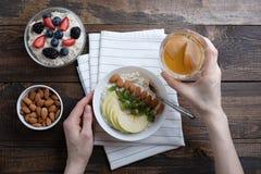 Hoogste mening van de handen van vrouwen in Ontbijt, havermeel met amandelen en Apple, noten, bessen, compote royalty-vrije stock fotografie