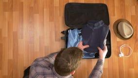 Hoogste mening van de jonge mens die kleren voor reis voorbereiden en het inpakken in koffer stock videobeelden