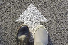 Hoogste mening van de mens die zwart-witte schoenen dragen die een manier duidelijk met witte pijlen kiezen Kiest het juiste wegc stock afbeeldingen