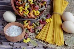 Hoogste mening van deegwaren, spaghetti, zout in een doos, peper en drie eieren die in het centrum van een donkere lijst liggen stock afbeelding