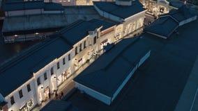 Hoogste mening van donkere dakbovenkanten, opslaggebouwen met verlichting en lopende mensen stock videobeelden