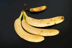 Hoogste mening van drie grote bananen en één minibanaan op zwarte achtergrond stock fotografie