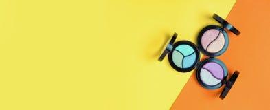 Hoogste mening van Drie Oogschaduwwenpallets en instrumenten op gele en oranje achtergrond Manier kosmetische reeks Hoogste menin stock afbeelding