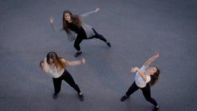 Hoogste mening van drie vrouwen dansende eigentijdse buitenkant in de zomer, actieve levensstijl stock videobeelden