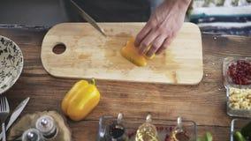 Hoogste mening van een chef-kok die een gele groene paprika snijden en het zetten in een kom stock video
