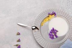 Hoogste mening van een fantastische milkshake Een plaat met een koele cocktail, bloemen en een lepel op een witte achtergrond De  stock foto's