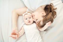 Hoogste mening van een gelukkige moeder die een baby kussen die op een bed liggen Stock Afbeeldingen