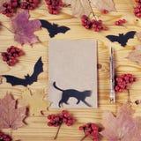 Hoogste mening van een houten bureau van Halloween Document, kat, pen, knuppels, bessen en esdoornbladeren Met exemplaarruimte Stock Afbeelding
