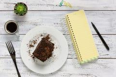 Hoogste mening van een houten lijst met leeg notitieboekje, koffie, cake en Royalty-vrije Stock Fotografie