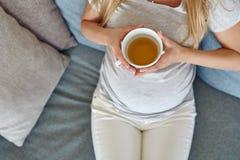 Hoogste mening van een jonge zwangere vrouw die op een comfortabele bank doen leunen stock afbeeldingen