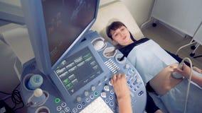 Hoogste mening van een jonge zwangere vrouw die ultrasone klank ondergaan stock videobeelden