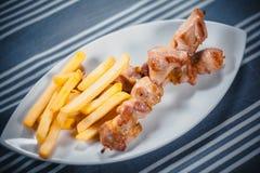 Hoogste mening van een kant-en-klare kebab en Frieten op een witte plaat Plaat op de lijst met een blauw binnen tafelkleed royalty-vrije stock foto