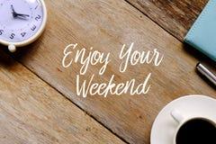 Hoogste mening van een kop van koffie, klok, notitieboekje en pen op houten die achtergrond met ENJOY wordt geschreven UW WEEKEND stock fotografie
