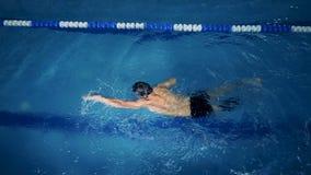 Hoogste mening van een mannelijke zwemmer met een prothetisch been in een zwembad stock videobeelden