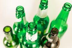 Hoogste mening van een pak lege groene en bruine wijn en bierglasflessen, met gescheurde etiketten op een witte achtergrond herge stock fotografie