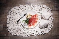 Hoogste mening van een plaat met traditionele voorgerechten Besnoeiingsvlees, bladeren en roquefort op een houten achtergrond Het Royalty-vrije Stock Fotografie
