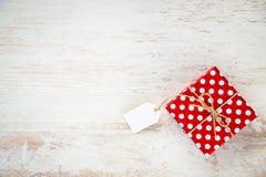 Hoogste mening van een rode gestippelde giftdoos over witte houten achtergrond De ruimte van het exemplaar Lege Nota Stock Foto
