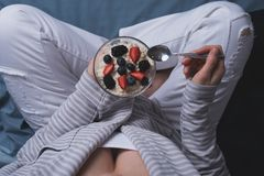 Hoogste mening van een vrouwenzitting in bed heb een gezond Ontbijt van havermeel en bessen royalty-vrije stock foto