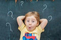 Hoogste mening van een weinig blonde jong geitjejongen met vraagteken op bord Concept voor verwarring, brainstorming en keus stock afbeelding