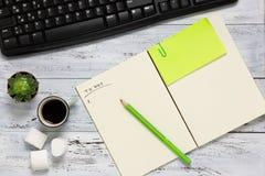 Hoogste mening van een werkruimte met open leeg notitieboekje Royalty-vrije Stock Foto's