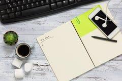 Hoogste mening van een werkruimte met open leeg notitieboekje Stock Afbeeldingen