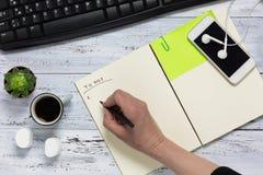 Hoogste mening van een wit houten bureau Hand die lijst, kop van schrijven te doen Royalty-vrije Stock Afbeeldingen