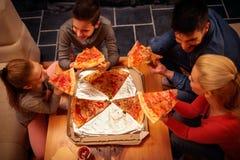 Hoogste mening van familie die pizzaplakken voor het diner eten Royalty-vrije Stock Afbeeldingen