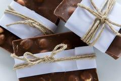 Hoogste mening van gebroken die chocoladestukken in Witboek en rustieke streng worden verpakt stock foto