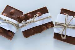 Hoogste mening van gebroken die chocoladestukken in Witboek en rustieke streng worden verpakt stock fotografie
