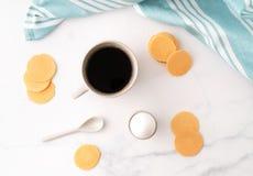 Hoogste mening van gekookt ei in ceramisch eierdopje, kop van koffie en dunne knapperige graanspaanders op achtergrond van mooi w royalty-vrije stock fotografie