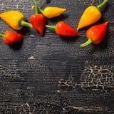 Hoogste mening van gele en roodgloeiende Spaanse peperpeper op barsten zwarte bac stock afbeeldingen