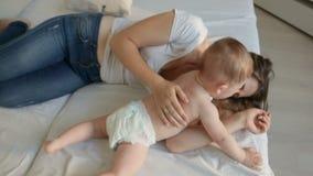 Hoogste mening van gelukkige jonge moeder die haar babyzoon op bed kietelen stock footage
