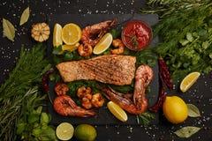 hoogste mening van geroosterd zalmlapje vlees, garnalen, stukken citroen, saus en kruiden op zwarte oppervlakte royalty-vrije stock afbeeldingen